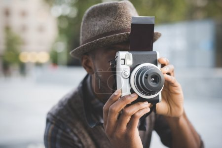 afro black man holding instant camera