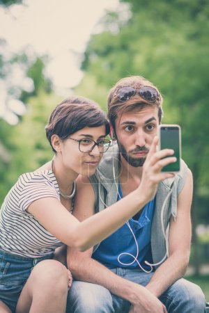 Photo for Couple of friends young  man and woman using smartphone in the city - Royalty Free Image