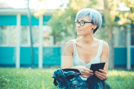 young beautiful short blue hair hipster woman using tablet