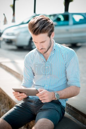 young handsome hipster modern man outdoor using tablet