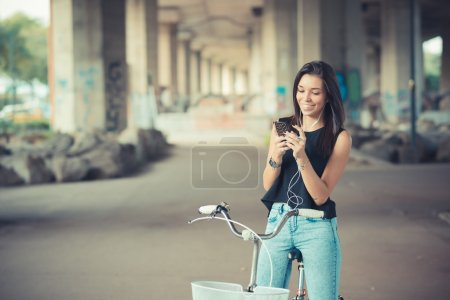 young beautiful brunette straight hair woman using bike and smar