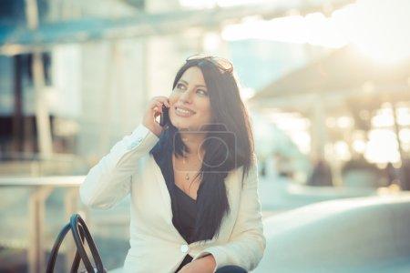 Foto de Hermoso pelo largo negro elegante mujer de negocios en la ciudad - Imagen libre de derechos