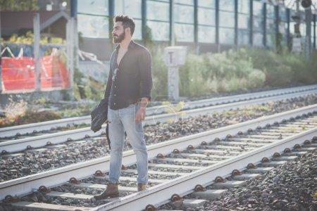 Photo pour Jeune homme beau modèle barbu attrayant debout sur le chemin de fer - image libre de droit