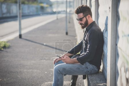 Photo for Young handsome attractive bearded man using smartphone in urban context - Royalty Free Image