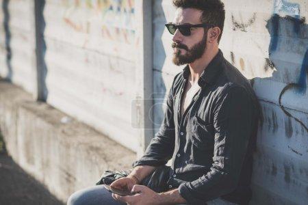 Photo pour Jeune bel homme barbu attrayant utilisant un smartphone dans un contexte urbain - image libre de droit