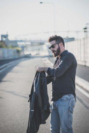 Photo pour Jeune bel homme barbu attrayant porte sa veste dans la rue dans un contexte urbain - image libre de droit