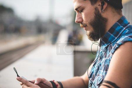 Photo pour Vue latérale du jeune homme hipster barbu beau utilisant un smartphone et écoutant de la musique avec des écouteurs dans la ville - image libre de droit