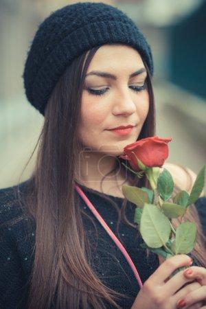 Photo pour Jeune belle femme brune avec rose rouge en plein air - image libre de droit