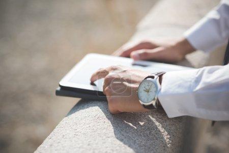 Photo pour Fermer la main de l'homme d'affaires à l'aide d'une tablette extérieure - image libre de droit
