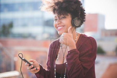 Photo pour Belle femme africaine aux cheveux bouclés noirs souriant et écoutant de la musique dans les écouteurs avec les pouces en ville - image libre de droit
