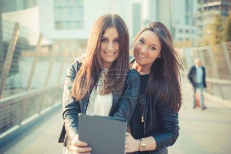 Two young beautiful women friends in town