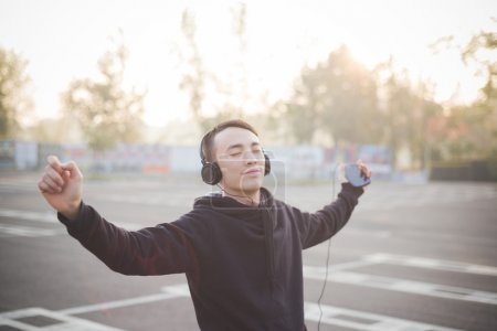 Young asian man in headphones dancing