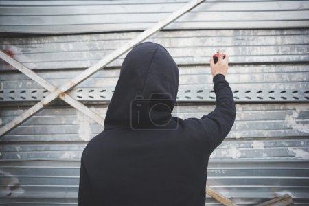 Photo pour Young asian hip hop man in town with graffiti spray drawing graffiti - image libre de droit