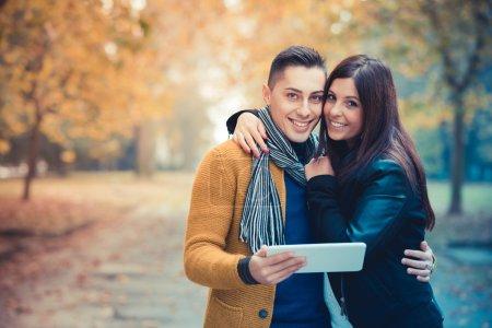 Photo pour Jeune couple dans le parc pendant la saison d'automne, en plein air - à l'aide de tablette, dispositif technologique - image libre de droit
