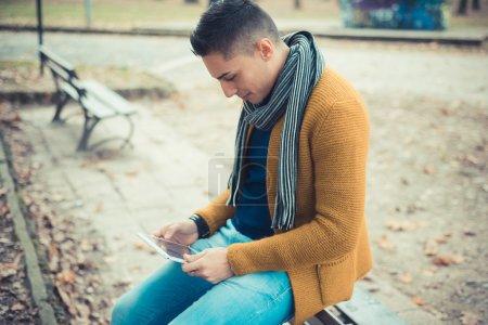 handsome man in park using tablet