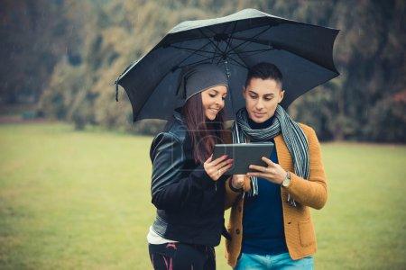 Photo pour Jeune couple dans le parc pendant la saison d'automne en plein air - à l'aide de tablette dispositif technologique pendant la pluie sous parapluie - image libre de droit
