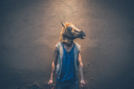 Photo for Hipster gay man in horse mask on dark wall background - Royalty Free Image