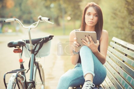 Photo for Young beautiful brunette straight hair woman using tablet outdoor - Royalty Free Image