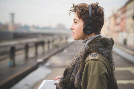 Photo pour Jeune belle femme hipster cheveux courts en ville en utilisant un appareil technologique tablette, connecté sans fil - image libre de droit