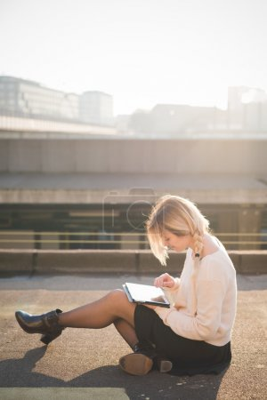 blonde woman outdoor using tablet