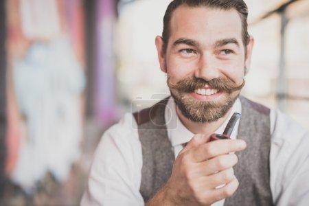 Photo pour Beau grand moustache hipster homme pipe à fumer dans la ville - image libre de droit