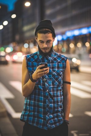 Photo for Young handsome bearded hipster man using smartphone and listening music with earphones in the city - Royalty Free Image