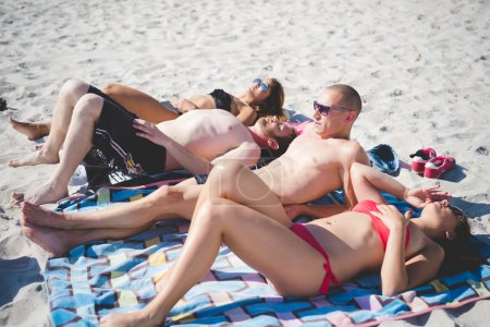 Photo for Group of young multiethnic friends women and men at the beach in summertime - Royalty Free Image