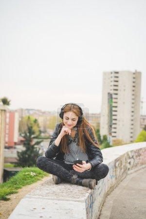 Photo pour Jeune fille brune de l'Est handosme écouter de la musique dans le parc de la ville - technologie, liberté, concept d'émancipation - image libre de droit