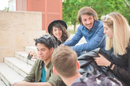 Photo pour Groupe de jeunes amis multiethniques, assis sur un escalier en discutant entre eux, avec planche à roulettes, s'amuser, sourire - amitié, concept de détente - image libre de droit