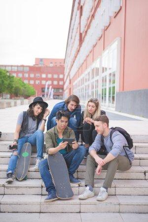 Photo pour Groupe de jeunes amis multiethniques assis sur un escalier avec planche à roulettes, parlant les uns aux autres, à l'aide d'un smartphone, amusez - amitié, concept de détente - image libre de droit