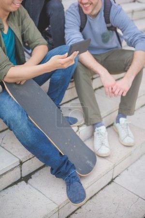Photo pour Groupe de jeunes amis multiethniques, assis sur un escalier de parler entre eux, à l'aide d'un smartphone, s'amuser - amitié, concept de détente - bouchent oh main sur smartphone et sur une planche à roulettes - image libre de droit