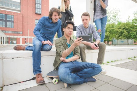 Photo pour Groupe de jeunes amis multiethniques assis sur un muret, parlant les uns aux autres, à l'aide d'un smartphone, visionnage d'une vidéo, amusez - amitié, concept de détente - image libre de droit