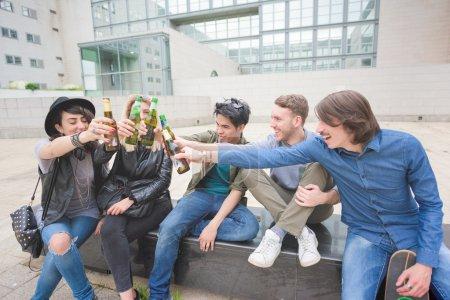Photo pour Groupe de jeunes amis multiethniques, assis sur un muret faire un toast avec bières, s'amuser - détente, le happy hour, le concept d'amitié - image libre de droit