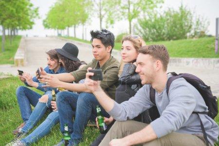 Photo pour Groupe de jeunes amis multiethnique sittingin un parc, parler entre eux, à l'aide d'un smartphone, s'amuser - amitié, concept de détente - image libre de droit