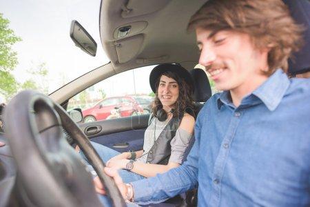 Photo pour Couple de jeune bel homme et une femme conduire une voiture, s'amuser, vous cherchez à huis clos, souriant - relaxant, le concept de bonheur - image libre de droit