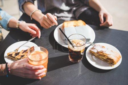 Photo pour Deux amies ayant un apéritif dans un bar - accent mis sur la table avec un gâteau, pain grillé et jus - apéritif, snack, concept de détente - image libre de droit