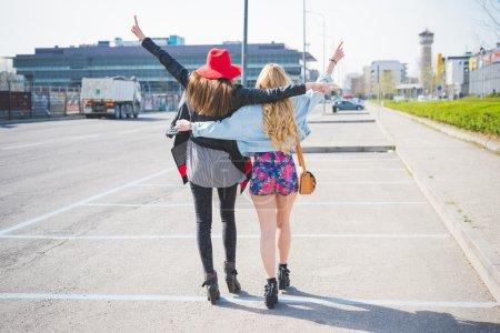 Photo pour Deux belles blondes et Brunettes amis remontant à travers la ville, étreindre, mains en l'air, s'amuser - amitié, émancipation, notion de bonheur - vue de dos - image libre de droit