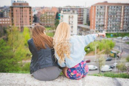 Photo pour Deux jeunes filles blondes et Brunettes chat assis sur un muret avec ville sur fond, vue de dos, un indiquant quelque chose sur la gauche - amitié, la notion d'insouciance - image libre de droit