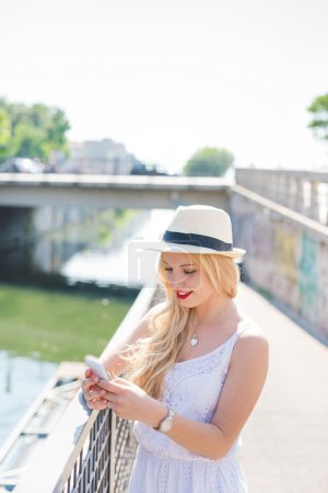 Photo for Half length of young blonde straight hair caucasian woman leaning on a handrail, using smartphone, looking downward the screen smiling - technology, communication, social network concept - Royalty Free Image