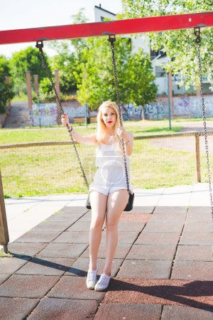 Photo pour Jeune longue blonde cheveux raides femme qui s'amuse sur une balançoire dans une aire de jeux regardant à la caméra, souriant enfance, fraîcheur, concept d'insouciance - image libre de droit