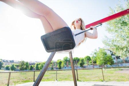 Photo pour Jeune beau caucasien longue blonde cheveux raides femme s'amuser sur une balançoire dans une aire de jeux regardant vers le haut - enfance, fraîcheur, concept d'insouciance - image libre de droit