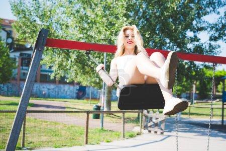 Photo pour Jeune beau caucasien longue blonde cheveux raides femme qui s'amuse sur une balançoire dans une aire de jeux regardant à la caméra, souriant enfance, fraîcheur, concept d'insouciance - image libre de droit