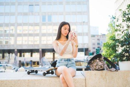 Photo pour Jeune belle asiatique long brun cheveux raides femme assise sur un petit mur, prendre selfie en plein air dans la ville avec smartphone, regardant vers le bas l'écran vanité, la technologie, concept de réseau social - image libre de droit