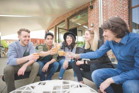 Photo pour Groupe de jeunes amis multiethniques s'asseyant dans un bar faisant un toast avec des bières, s'amusant - détendant, happy hour, concept d'amitié - image libre de droit