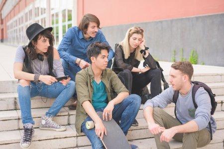 Photo pour Groupe de jeunes amis multiethniques, assis sur un escalier parler entre eux, avec planche à roulettes, amusez - amitié, concept de détente - image libre de droit