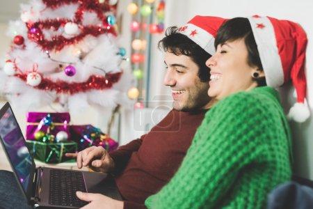 Photo pour Demi-longueur de jeune beau couple homme et femme avec santa claus chapeau assis sur le canapé en utilisant l'ordinateur, écran de recherche, souriant - se concentrer sur l'homme - technologie, Noël, concept de réseau social - image libre de droit