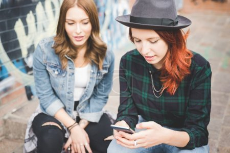 Photo for Half length of two young blonde and redhead straight hair women using smartphone, looking downward tapping the screen, smiling - communication, social network, technology concept - Royalty Free Image