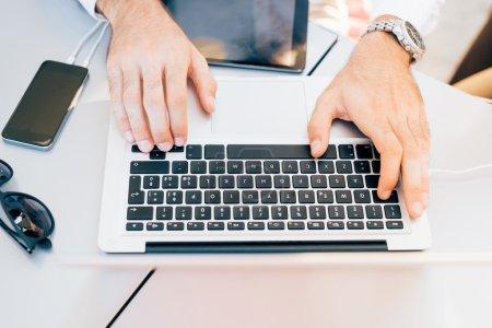 Photo pour Vue de dessus de près sur les mains d'un jeune homme d'affaires beau en utilisant des appareils technologiques tels que ordinateur portable, smartphone et tablette - communication, entreprise, concept de travail - image libre de droit