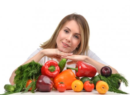 woman working at desk with fresh fruits and vegetables happy smi