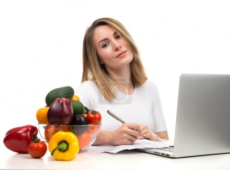 Confident nutritionist woman working at desk with fresh fruits a